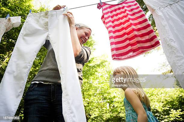 Smiling mother and child hanging clothes outside together