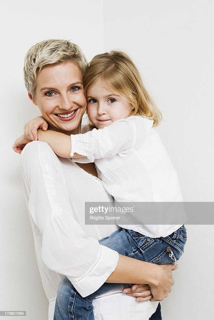 Smiling mother and daughter hugging : Stock Photo