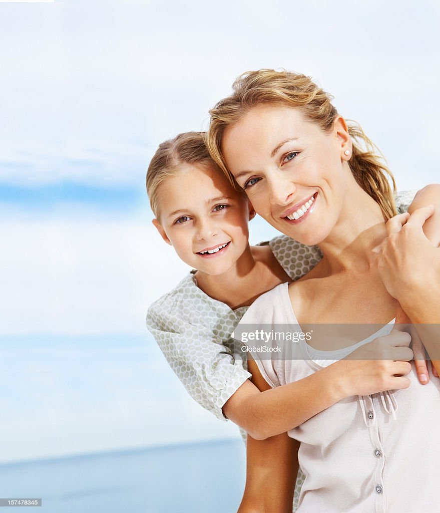 Smiling mother and daughter in a loving embrace on the beach : Stock Photo