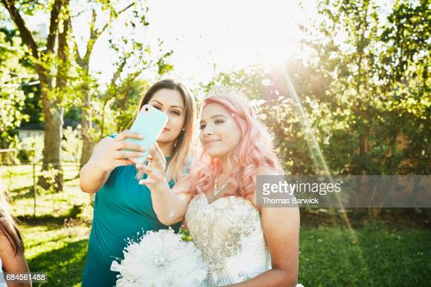 Smiling mother and daughter in quinceanera gown taking selfie with smartphone in backyard