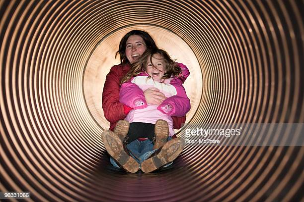 Smiling Mother and Daughter in the Tube Slide