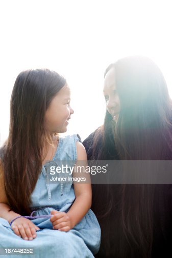 Smiling mother and daughter looking at each other : Stock Photo