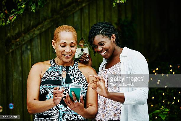 Smiling mother and daughter looking at smartphone