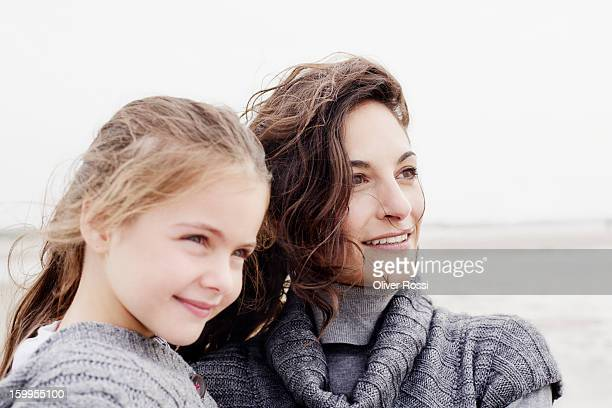 Smiling mother and daughter on the beach