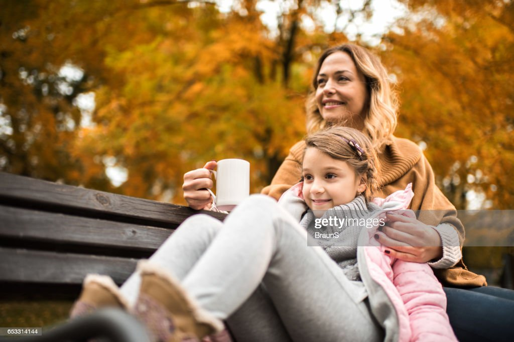 Smiling mother and daughter relaxing on a bench in autumn. : ストックフォト