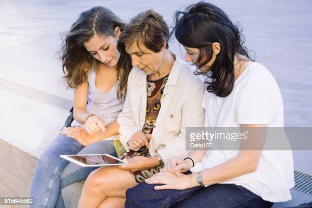 Smiling mother and daughters using a tablet sitting outdoors in a modern city-scape