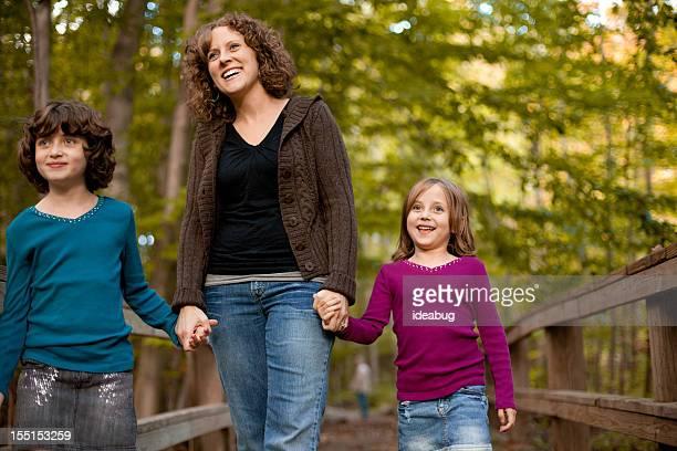 Sourire, mère et filles marchant sur un pont en plein air