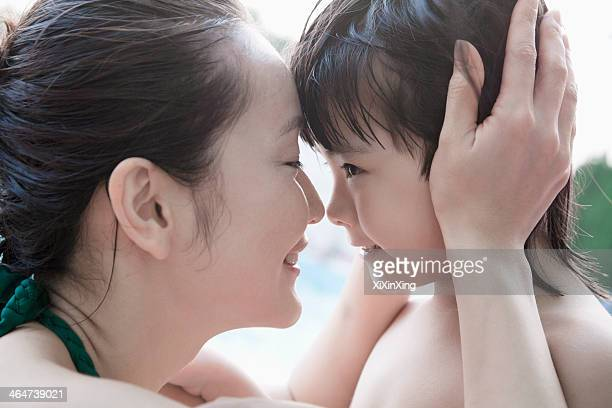 Smiling mother and son embracing and holding head by the pool