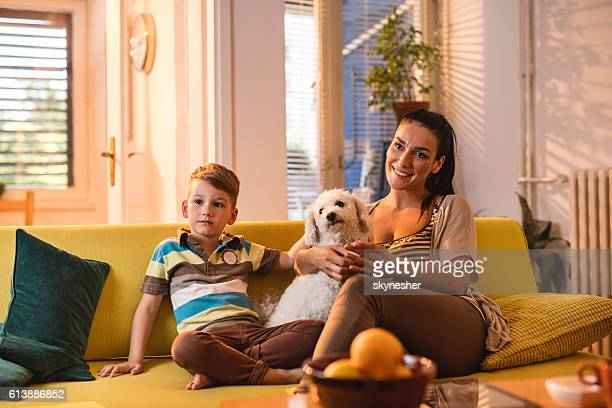 Smiling mother and son enjoying with their dog at home.