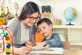 Kindergarten Teacher Supports Cute Boy in Educational Game Play, Smiling Mother and Son Playing and Learning Together at Home