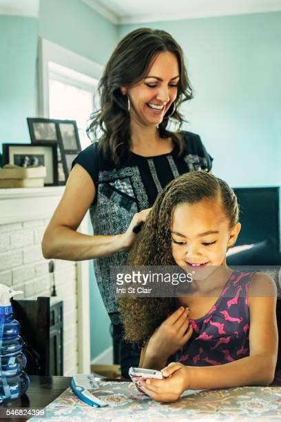 Smiling mother brushing hair of daughter