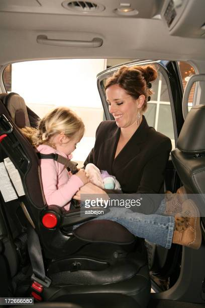 Smiling mother buckling her daughter into car toddler seat