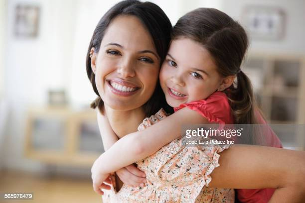 Smiling mother carrying daughter piggyback
