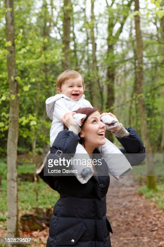 Smiling mother carrying son in forest