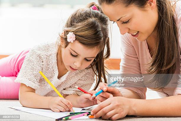 Smiling mother coloring with her daughter at home