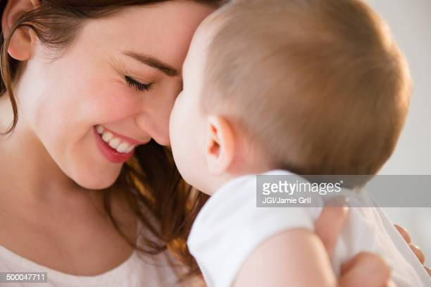 Smiling mother cradling baby