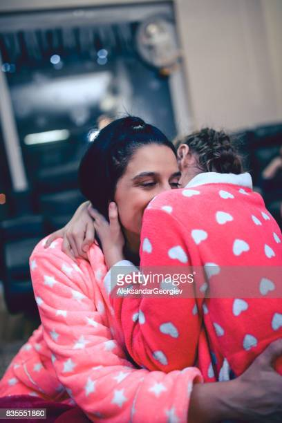 Smiling Mother Embracing her Daughter for Good Night Sleep