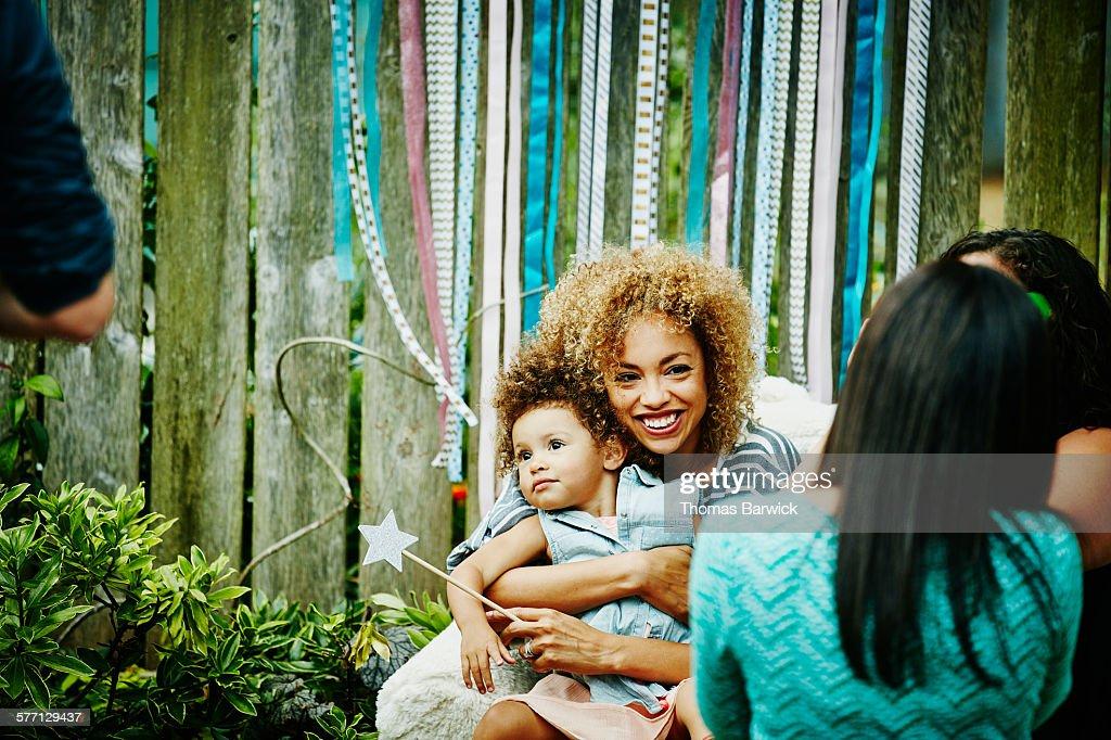 Smiling mother embracing toddler daughter