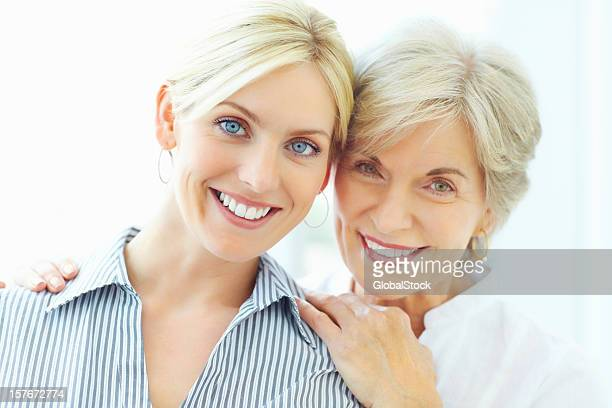 Smiling mother embracing young daughter from behind