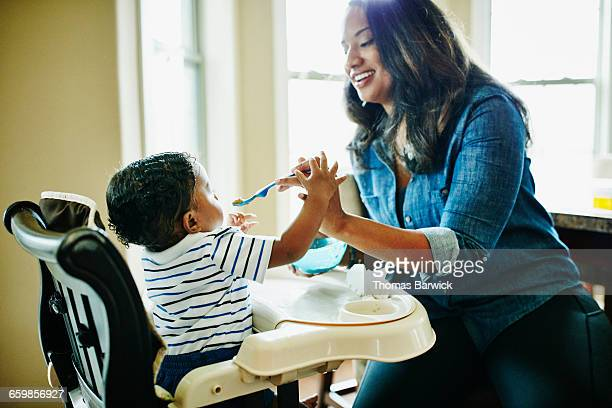 Smiling mother feeding infant son in highchair