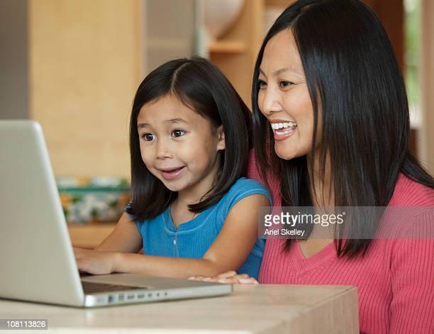 Smiling mother helping daughter on laptop