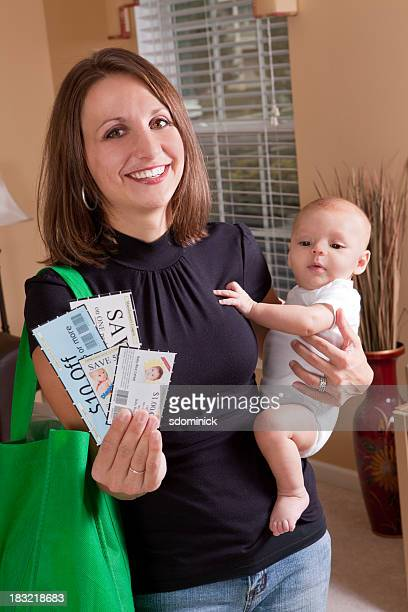 Smiling Mother Holding Baby And Coupons