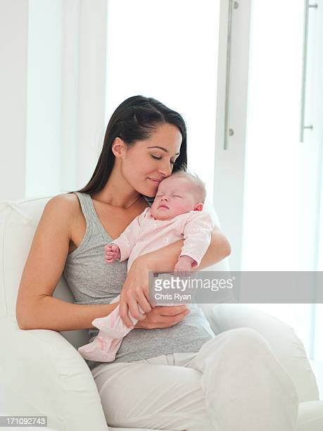 Smiling mother holding sleeping baby