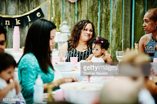 Smiling mother holding toddler daughter at party