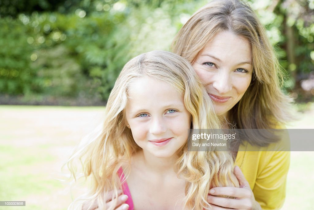 Smiling mother hugging daughter : Stock Photo