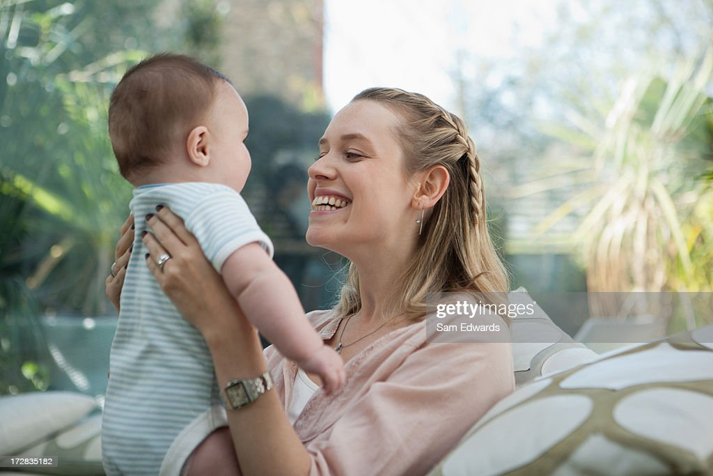 Smiling mother lifting baby son : Stock Photo