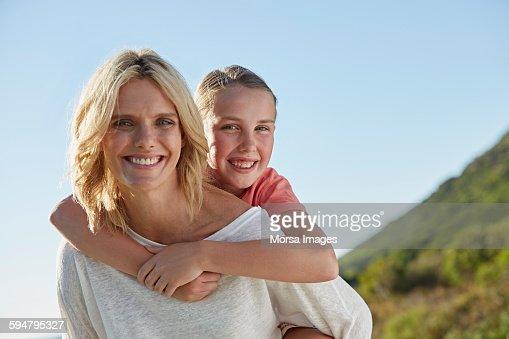 Smiling mother piggybacking daughter