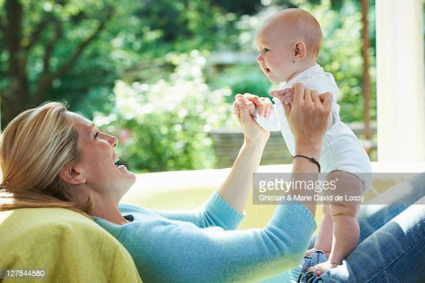 Smiling mother playing with baby