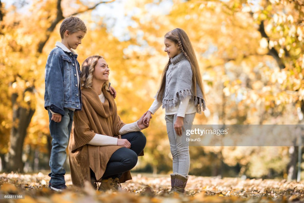 Smiling mother talking to her small kids in the park. : Stock Photo