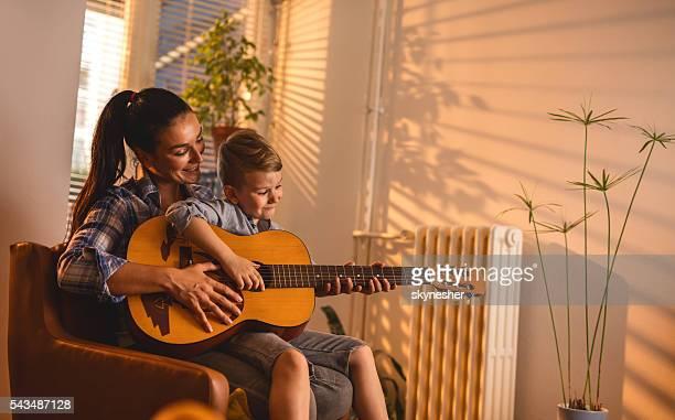 Souriante mère enseigner fils fils jouer de la guitare acoustique.