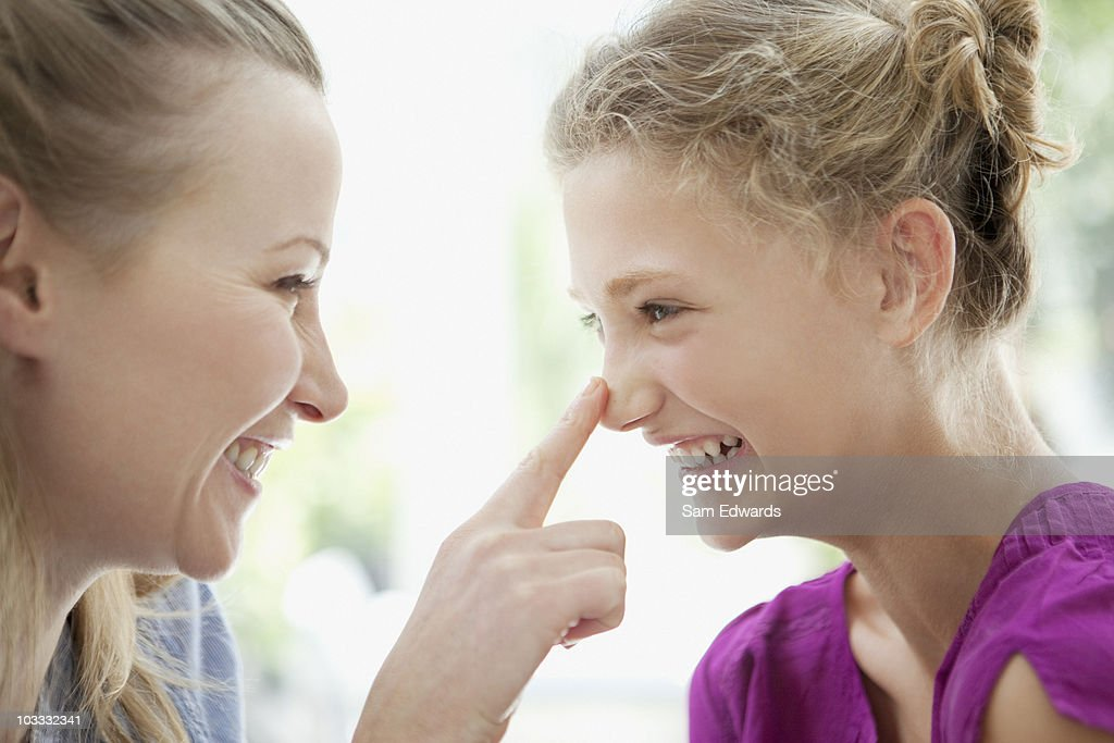 Smiling mother touching daughters nose : Stock Photo