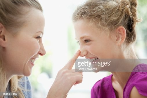 Smiling mother touching daughters nose