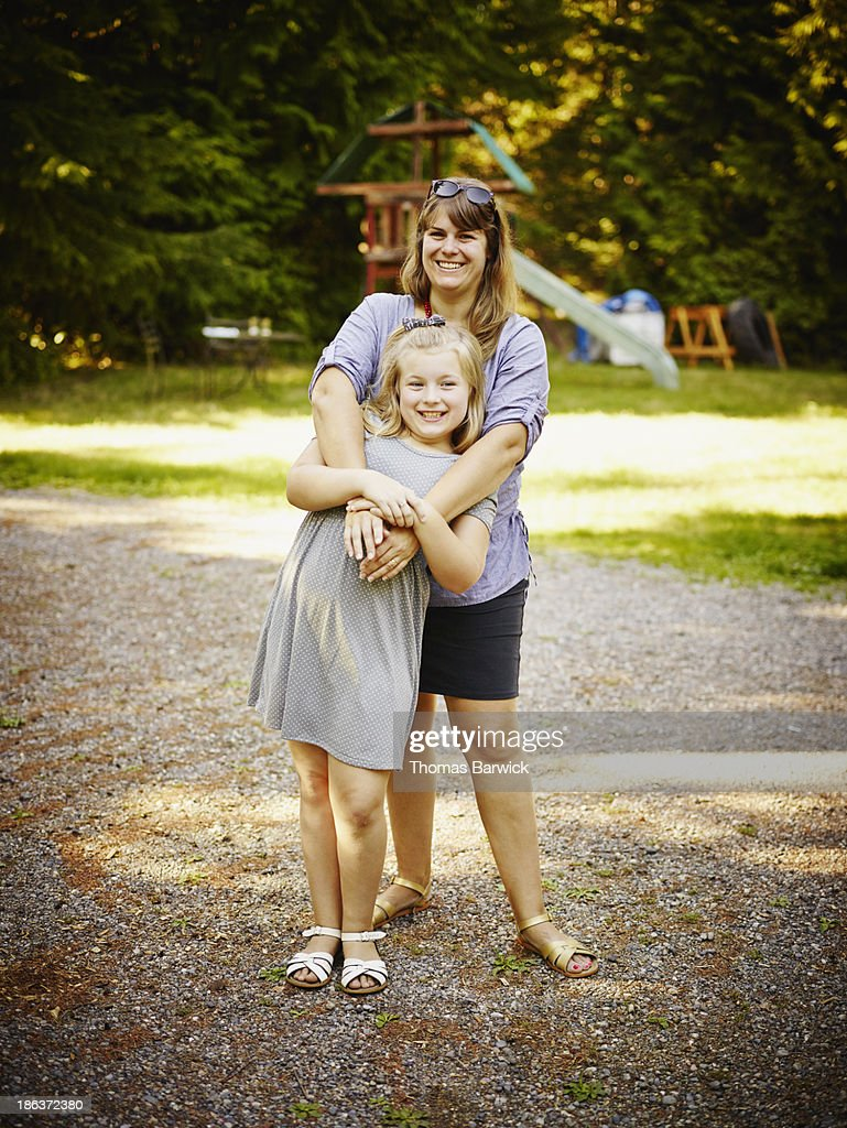 Smiling mother with arms around daughter : Stock Photo