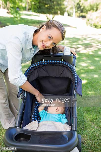 Lächelnd Mutter mit baby schlafen im Kinderwagen spazieren
