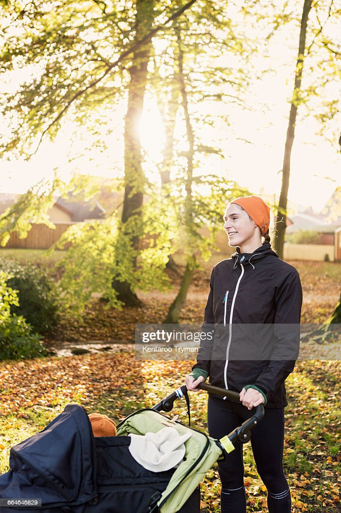 Smiling mother with baby stroller standing against trees