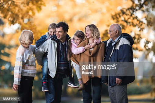 Smiling multi-generation family talking during autumn day in nature. : ストックフォト