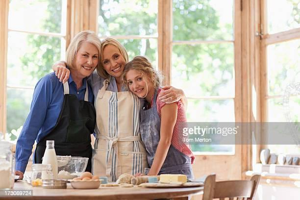 Smiling multi-generation females hugging in kitchen