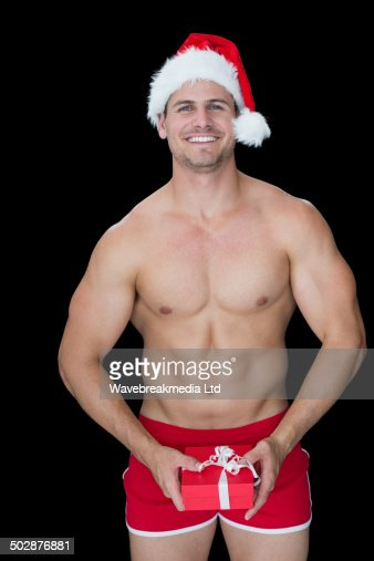 Smiling muscular man posing in sexy santa outfit holding gift : Foto de stock