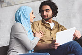 smiling muslim couple using tablet at home