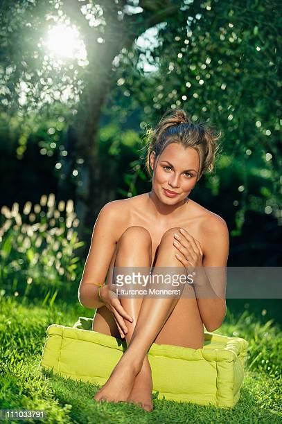 Smiling naked woman sitting in garden legs crossed