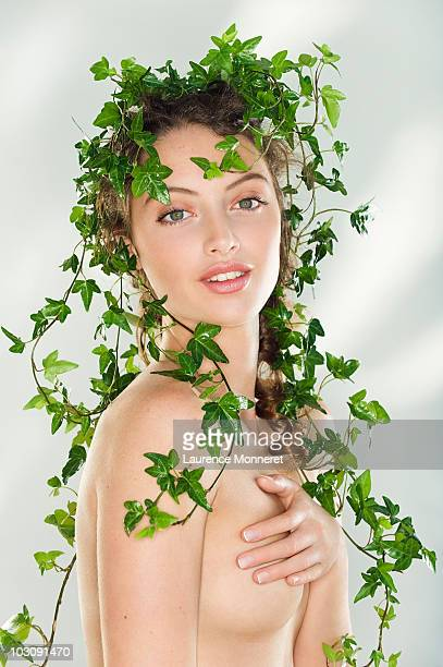 Smiling naked young woman covered with ivy