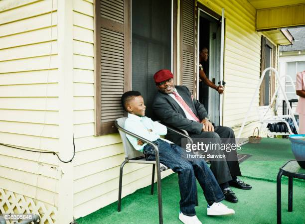 Smiling nephew and uncle sitting together on front porch of home