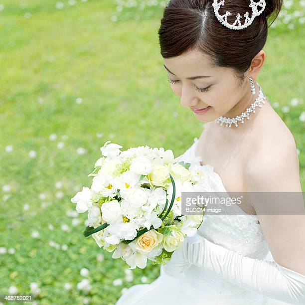 Smiling Newlywed Bride Looking At Bouquet