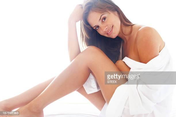 Chair de femme souriant enveloppé dans un drap contre blanc