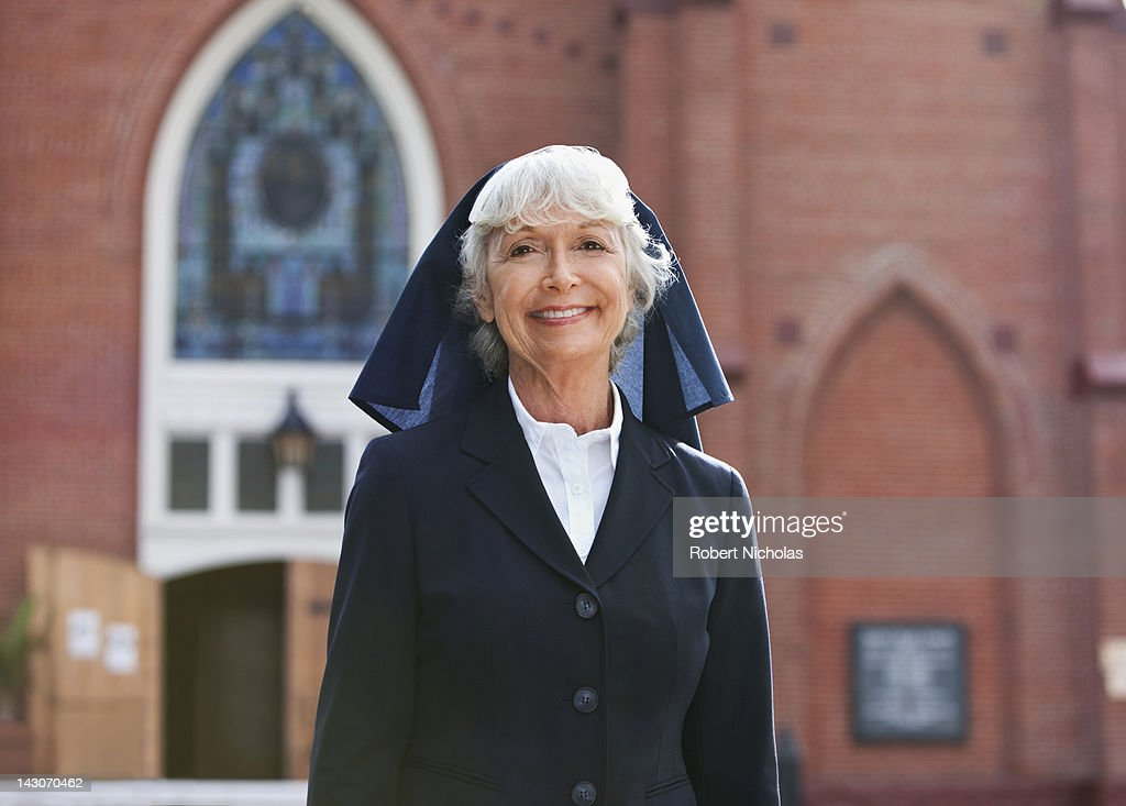 Smiling nun walking outdoors