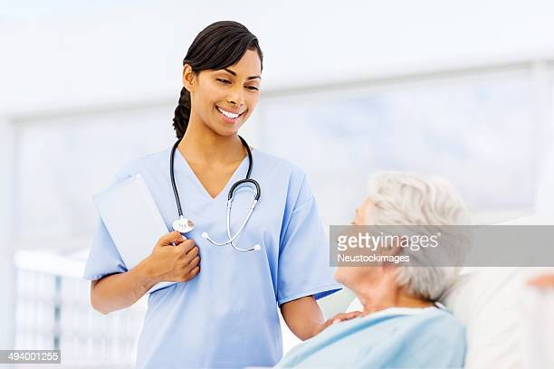 Smiling Nurse Consoling Female Patient In Hospital Ward